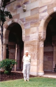 Dorothy Hill in 1987, standing below her sandstone grotesque where it adorns the Richards Building in the Great Court.